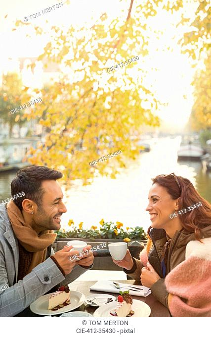 Young couple drinking coffee and eating cheesecake dessert at autumn sidewalk cafe along canal