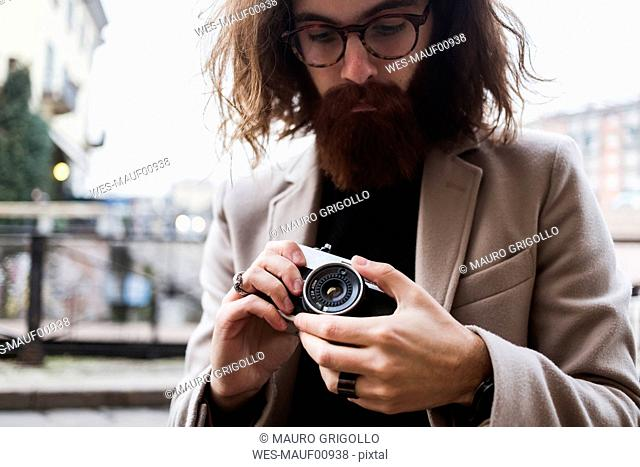 Stylish young man outdoors holding camera
