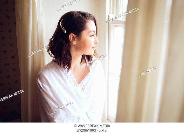 Beautiful woman looking out of the window