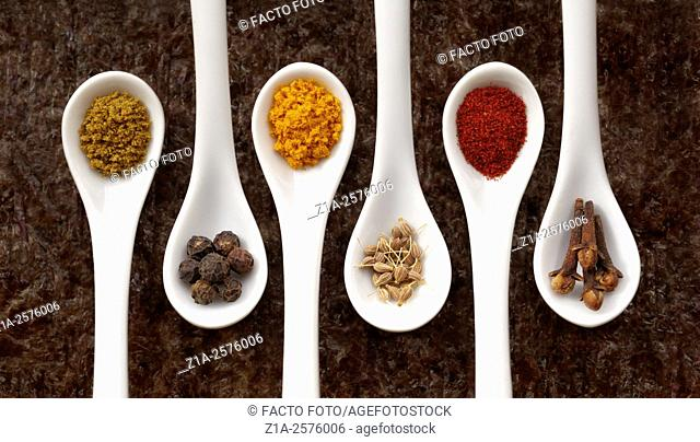 Five white spoons with assorted spices on a dark background