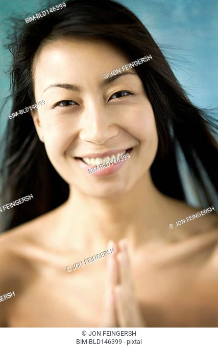 Smiling Chinese woman praying