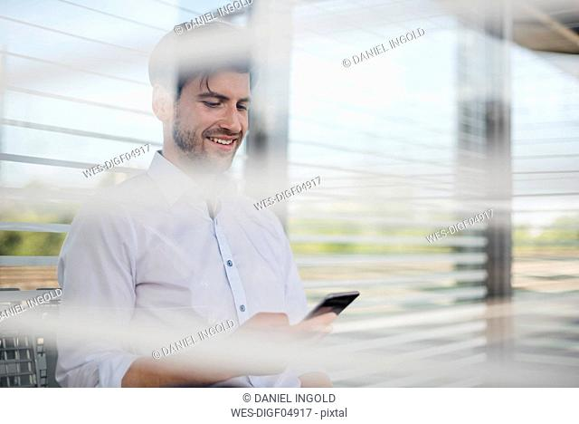 Smiling businessman on station platform using cell phone