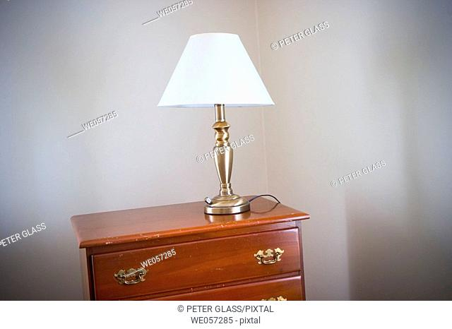 Lamp setting on top of a bureau in a bedroom
