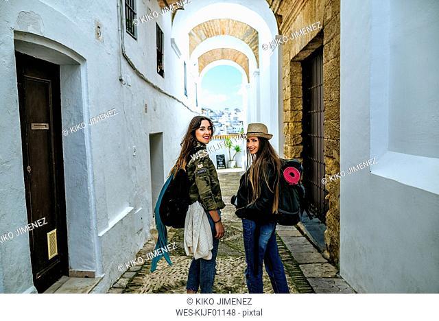Spain, Andalusia, Vejer de la Frontera, two young women walking in the alley El Callejon de las Monjas