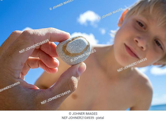 Hand holding rock, boy on background