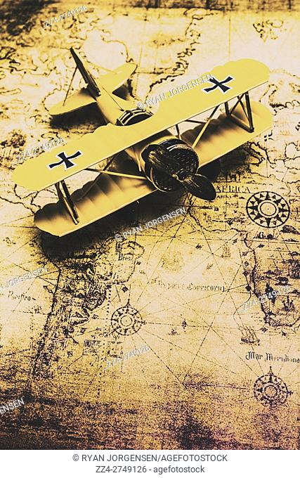 Aviator exploration concept with a vintage bi plane on old world map. Planes and global mapping