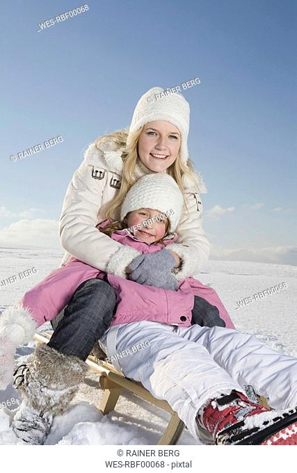 Germany, Bavaria, Munich, Mother and daughter 6-7 sitting on sledge, smiling, portrait