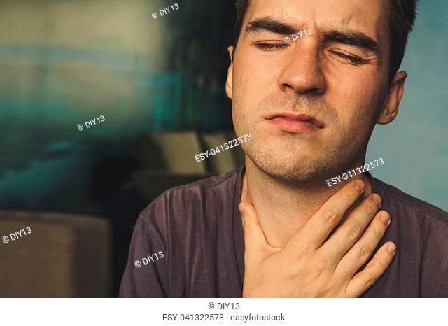 people, healthcare and problem concept. unhappy man touching his neck and suffering from throat pain while sitting on couch at home