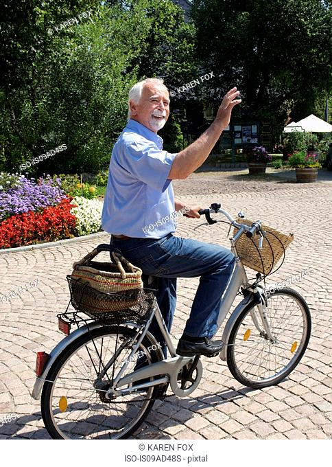 Senior man cycling through park