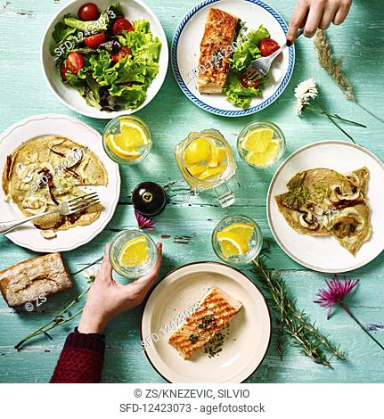A table laid for lunch with salmon, pancakes and a mixed leaf salad