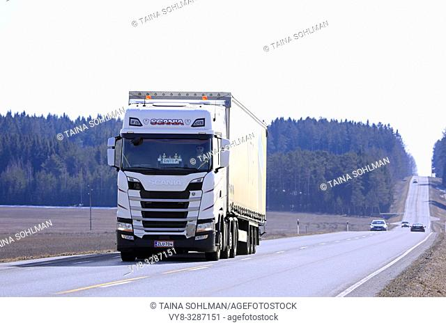 Jokioinen, Finland - April 6, 2019: White Next Generation Scania S500 semi trailer transports goods on highway 2 in Finland on a hazy day of spring