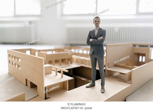 Miniature businessman figurine standing in architectural model
