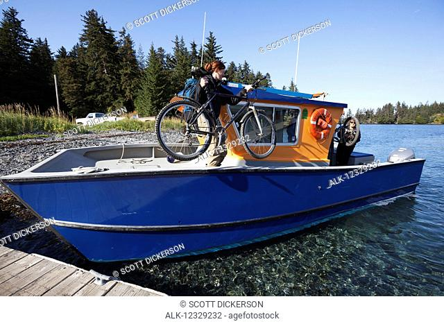Woman loads her bike on to a water taxi, Kenai Peninsula, South-central Alaska; Alaska, United States of America