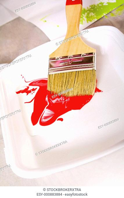 Image of paintbrush in tray with white and red colors