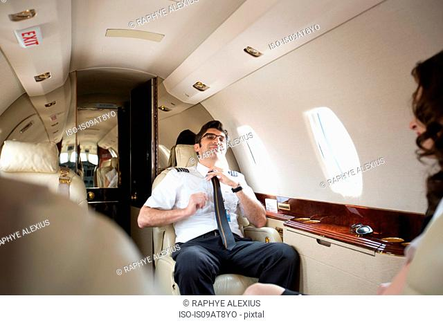 Male pilot loosening tie in cabin of private jet