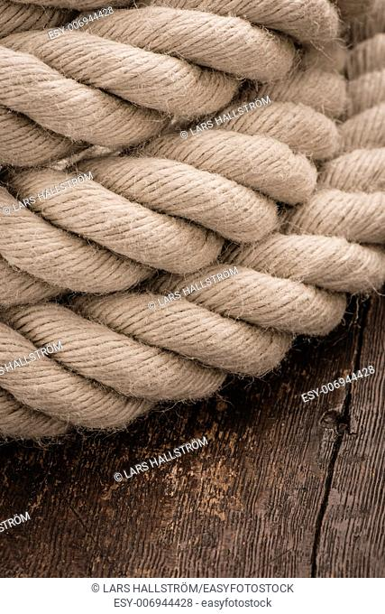 Close up of strong hemp rope on wooden background