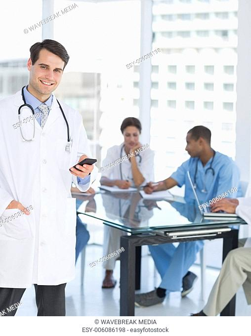 Doctor text messaging with group around table in hospital