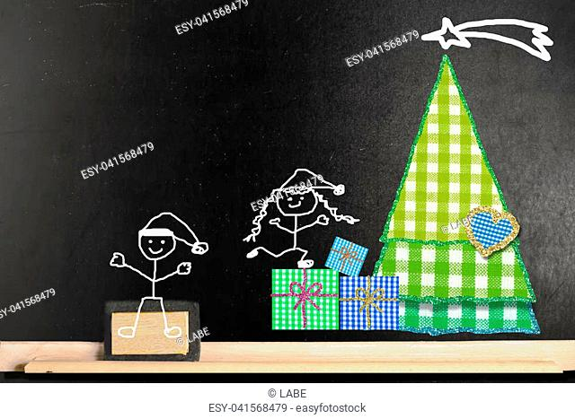 Fun Christmas card. Funny Christmas card. Happy boy and girl stickman and fabrics Chtistmas tree on a blackboard with copy space