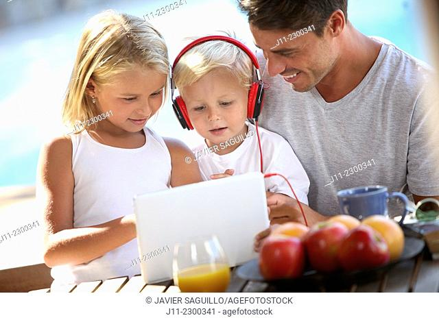 Family, children with digital tablet and headphones