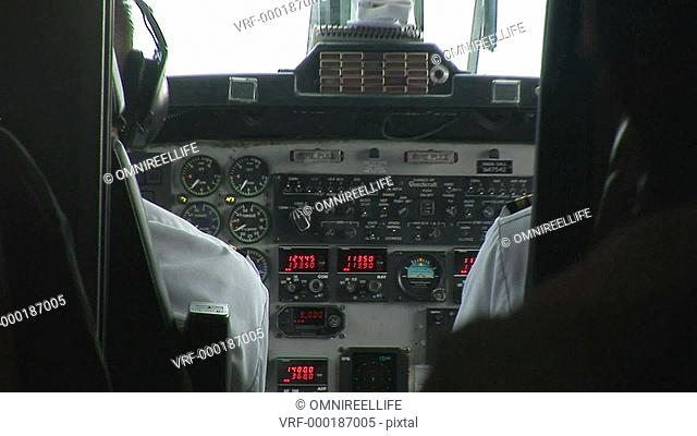View of cockpit of airplane and male pilots seen from aisle