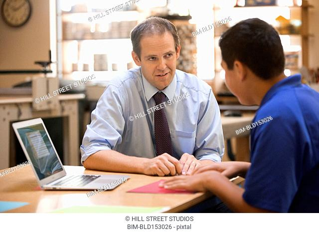Teacher helping student use laptop in class