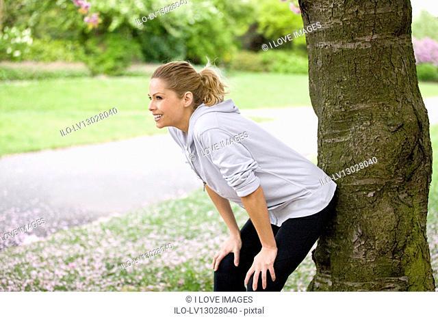 A female runner resting against a tree