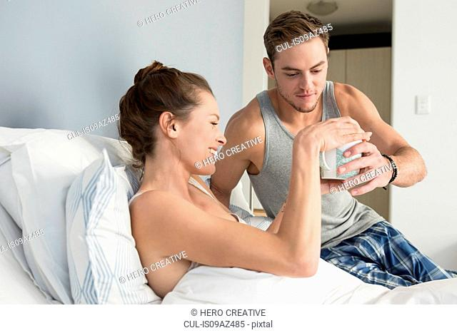 Young man handing coffee to girlfriend lying in bed