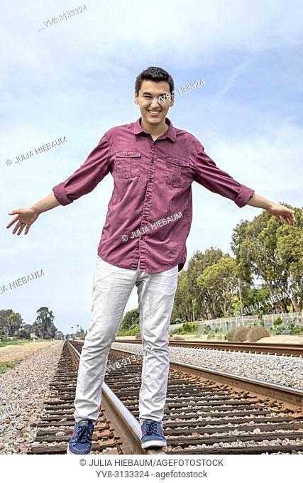 Young man balancing on railway traclks, Calsbad, California