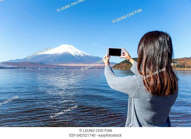 Woman taking photo in mount Fuji and Lake Yamanaka