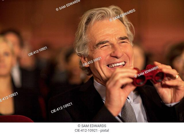 Man with opera glasses laughing in theater audience