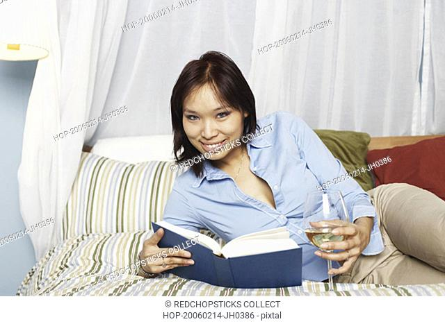 Portrait of a young woman holding a wineglass and a book on the bed