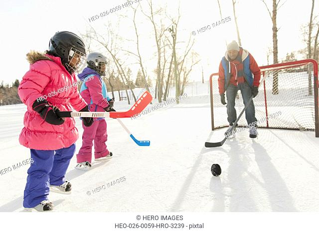 Father and daughters playing ice hockey