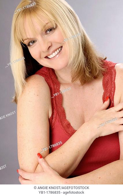 Healthy, confident woman in her 40s  She has nice teeth and a neat manicure with red fingernails