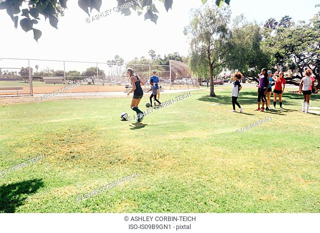 Male teacher doing soccer practice with schoolgirls on school sports field