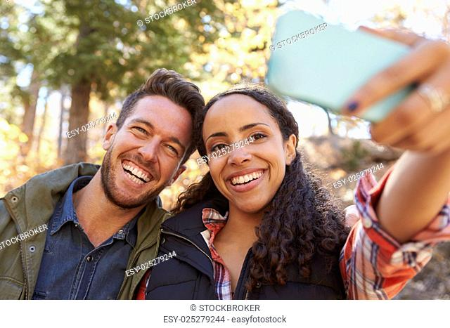 Laughing mixed race couple taking a selfie in a forest