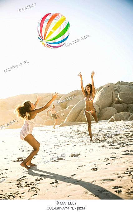 Mother and daughter playing ball on beach