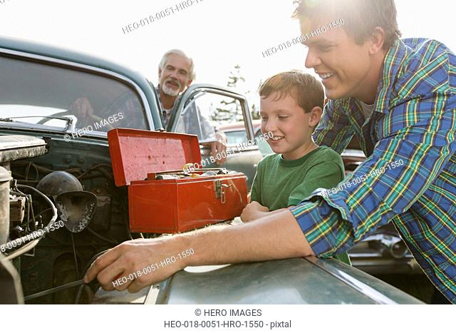 Three generations of males working on classic car