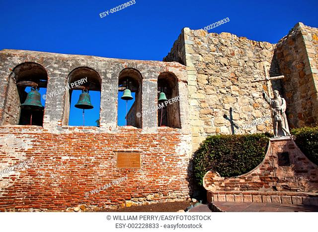 Mission San Juan Capistrano Church Ruins in California Brass Bells and Statue of Father Junipero Serra, who founded the Mission in 1775 Church was destroyed in...