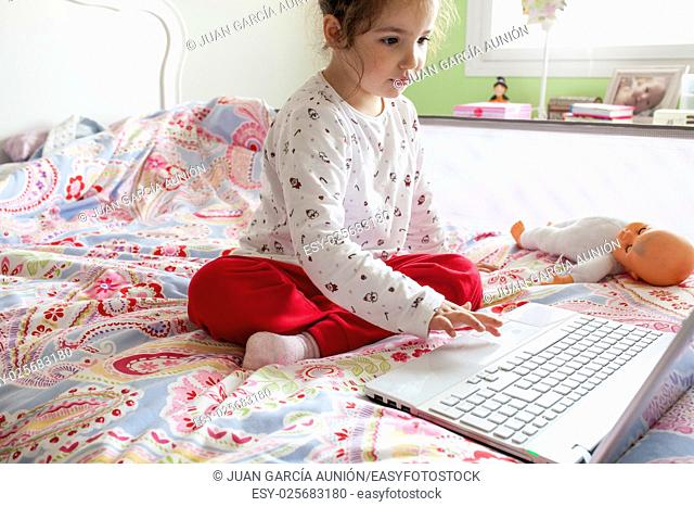 Little girl sitting in bed and surfing on Internet in her bedroom. Parental control concept