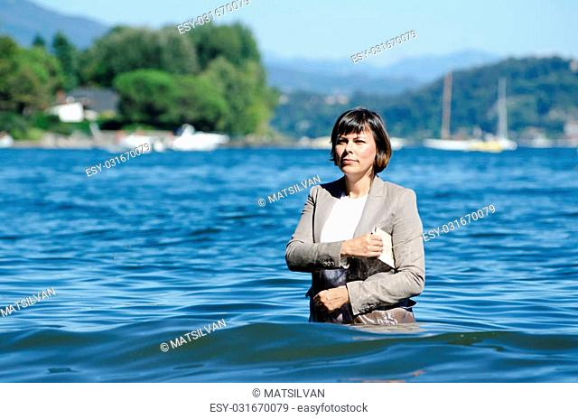 Business woman standing in the lake with her clothes on and a financial newspaper under her arm