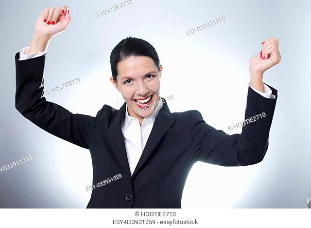 Beautiful jubilant young businesswoman cheering with a beaming enthusiastic smile on her face as she celebrates a success, with copyspace