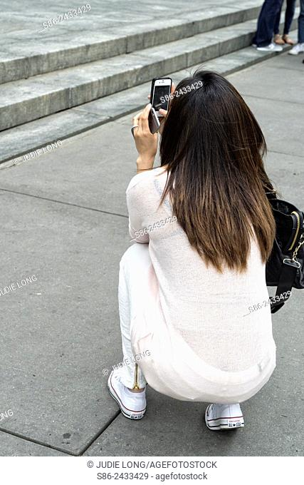 Young Woman squatting to take a photo with her smartphone camera