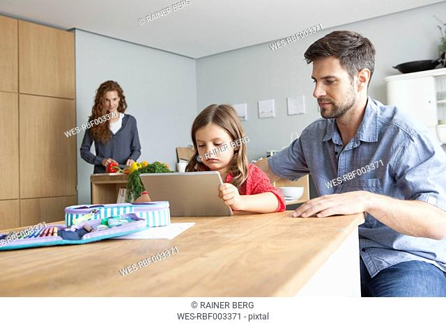 Little girl and her father sitting at kitchen table looking at digital tablet
