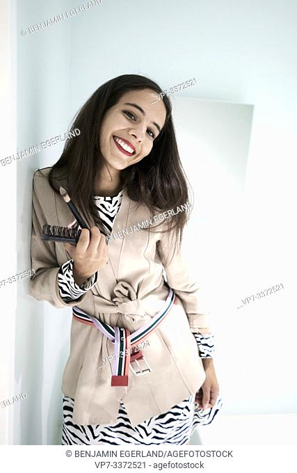 stylish woman smiling in bathroom, holding comb