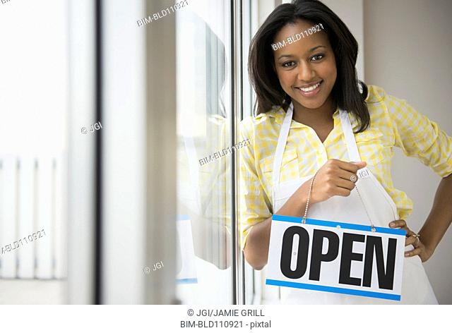 African American business owner with ,'open' sign