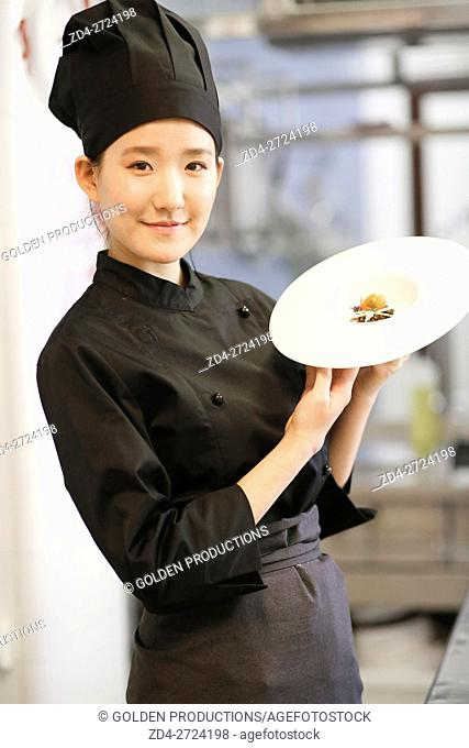 Cook presenting plate with small amount of food