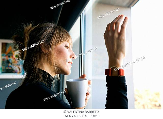 Young woman drinking cup of coffee looking out of window