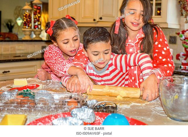 Children in kitchen wearing pyjamas rolling out dough with rolling pin