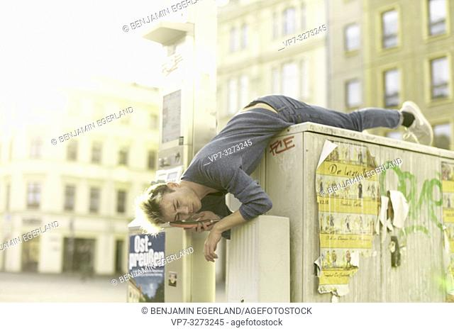 young man lying upside down, calling with payphone, inconvenient, in city Cottbus, Brandenburg, Germany