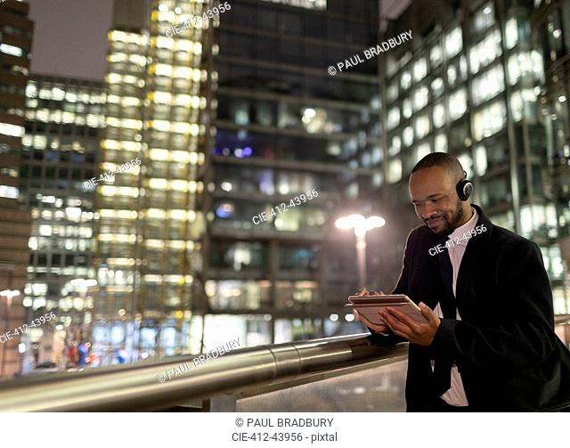 Businessman with headphones using digital tablet on urban pedestrian bridge at night
